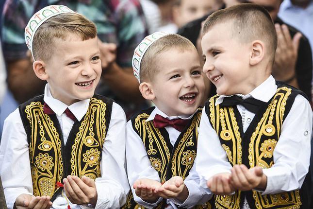 anak-anak mengenakan rompi hitam yang dihiasi dengan benang emas dan dasi kupu-kupu saat Idul Fitri.